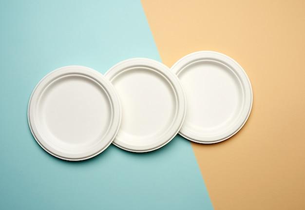Стопка белой бумаги одноразовых тарелок на бежево-голубом фоне, вид сверху