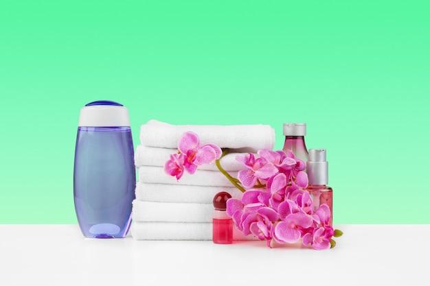 白いテーブルの上の白いタオルとスキンケアのボトルのスタック