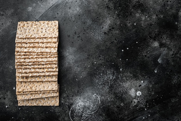 해바라기, 치아 및 sesames 씨앗 세트, 전체 곡물 바삭한 빵의 스택, 검은 어두운 돌 테이블 배경, 상위 뷰 평면 누워, 텍스트 복사 공간