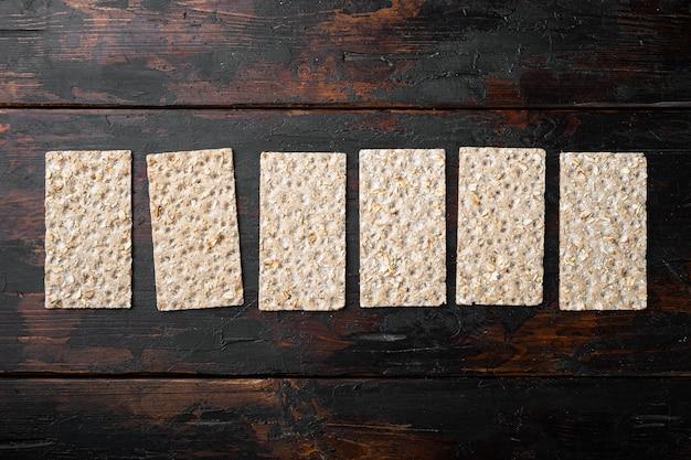 Стопка цельнозернового хрустящего хлеба с набором семян подсолнечника, чиа и кунжута, на старом темном деревянном столе, плоская планировка, вид сверху