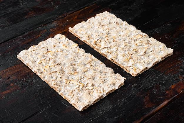 Стопка цельнозернового хрустящего хлеба с набором семян подсолнечника, чиа и кунжута, на старом темном деревянном столе