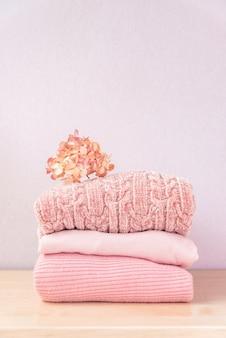 冬や秋の婦人服のスタック。カラフルなニットの居心地の良い暖かいピンクのセーターや木製のテーブルのプルオーバーの山。