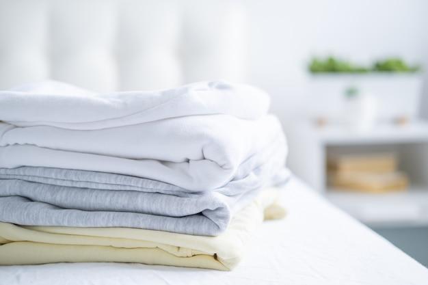 女性のカラフルなスウェットシャツ、白いベッドにパステルカラーのパーカーのスタック。季節のショッピング、ランドリー、休暇のコンセプト。