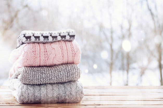 나무 tableon 겨울 배경에 양모 니트 옷의 스택