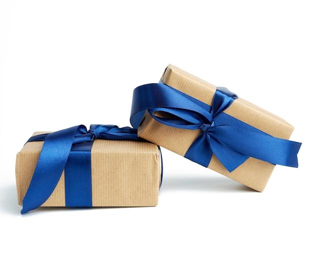 茶色のクラフトペーパーで包まれた箱のスタックし、シルクブルーのリボン、白い背景で隔離のホリデーギフトで結ば