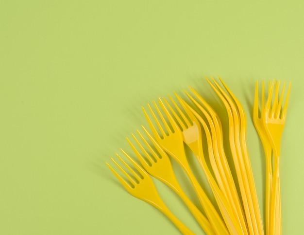 Стек желтых пластиковых вилок на зеленой поверхности, вид сверху, копия пространства