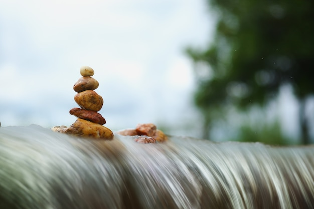 雲の嵐の背景の滝の上の禅の石のスタック