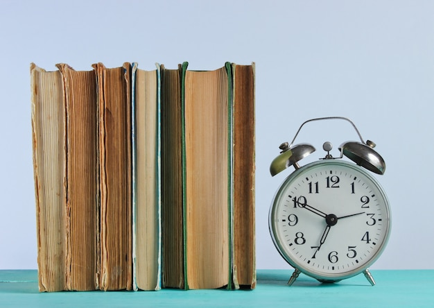 Stack of old books and alarm clock on woden shelf against the white wall