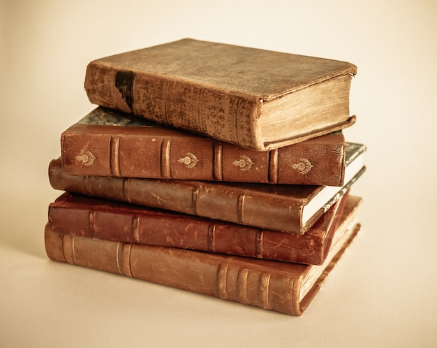 Stack of old books isolated on beige background