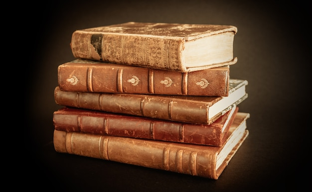 Stack of old books isolated on black background