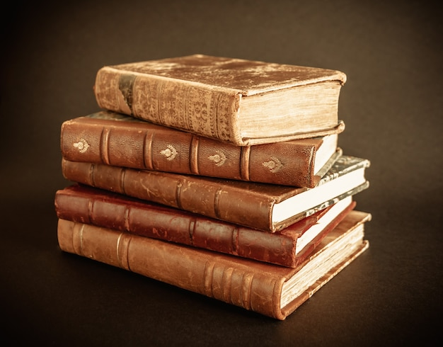 Stack of old books isolated on dark background