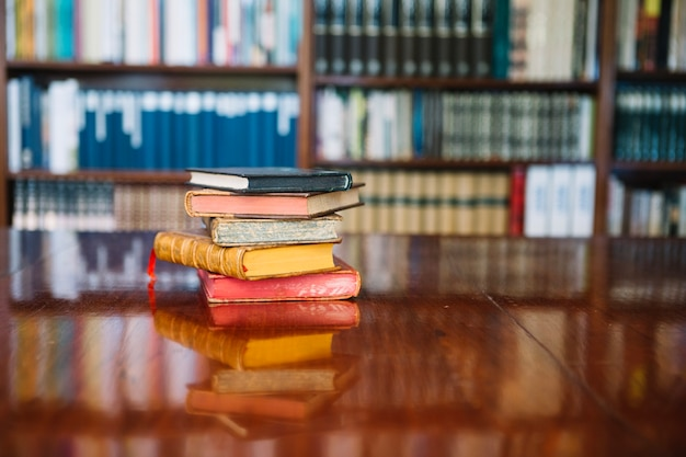 Stack of old books on library table