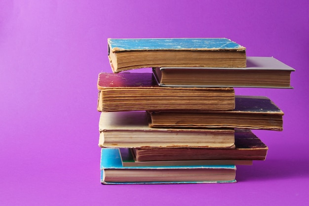 Stack of old books on purple table.