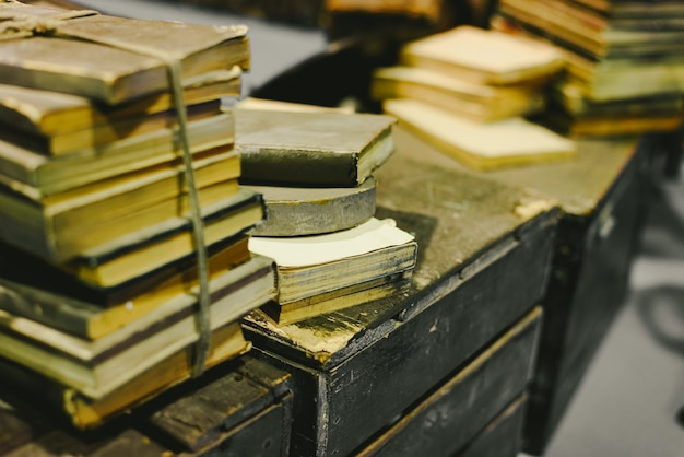 Stack of old books stored in disrepair on an old vintage trunk.