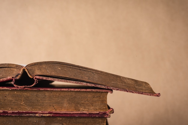 Stack of old books on vintage brown wall background