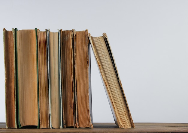 Stack of old books on woden shelf against the a white wall