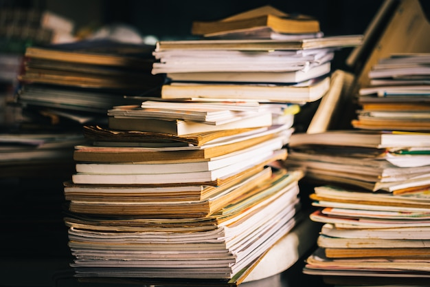Stack of old books on wooden table.