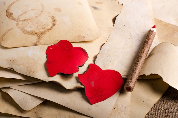 Stack old papers, notebook, wooden pencil and two vintage red hearts on burlap, sackcloth.