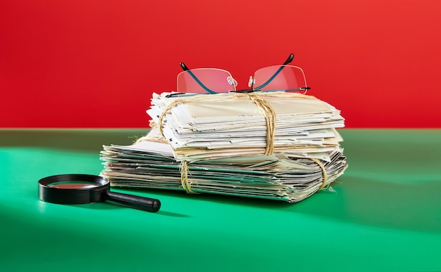 A stack of old photographs with glasses and a magnifying glass on a green table against a red background