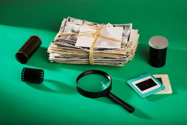 A stack of old photographs with negatives and a magnifying glass on a green background