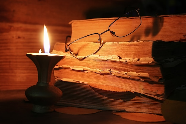 Stack of old tattered book on a wooden table lighted candle and glasses