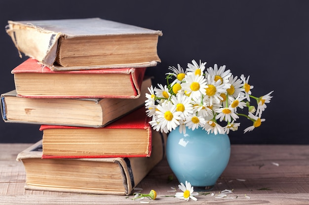 A stack of old vintage books lying on a wooden shelf with a bouquet of daisies in a blue vase.