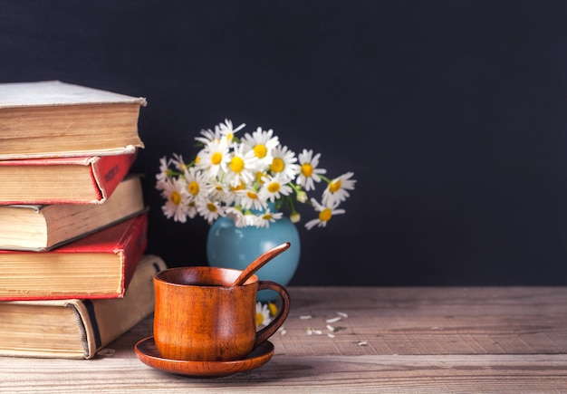A stack of old vintage books lying on a wooden table. country still life.