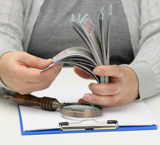A stack of one hundred dollar bills in a woman's hand and a wooden magnifying glass on a white table. budget analysis, income and expenses, problem finding