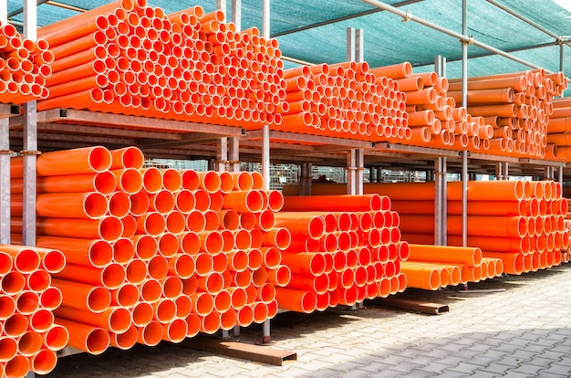 Stack of orange pvc water pipes in abandoned industrial area