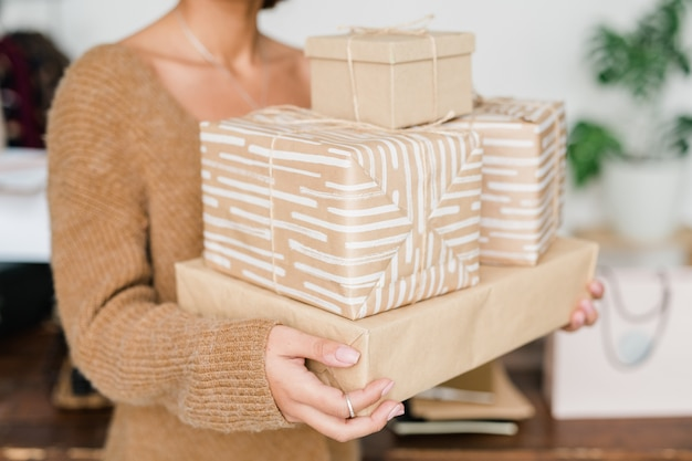 Stack of packed and wrapped giftboxes held by young casual woman in beige knitted pullover