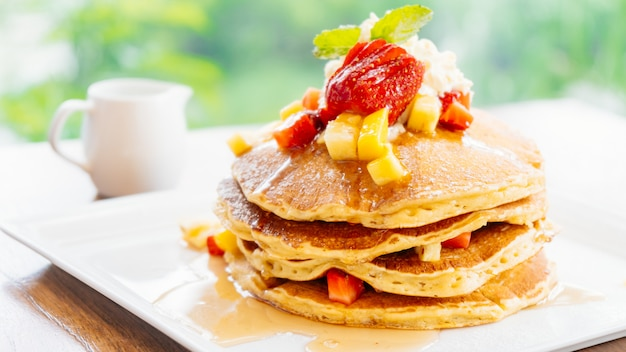 Stack of pancake with strawberry on top