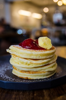 Stack of pancakes on black plate