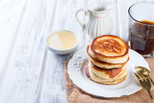 Stack of  pancakes in a dish on wooden white on