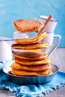 Stack of pancakes and some are hovering above the pan