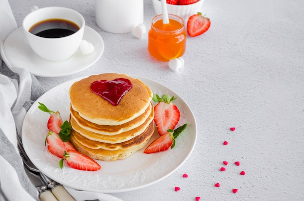 A stack of pancakes with a heart of jam on top with fresh strawberries and mint on a white plate on a light background.
