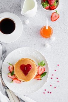 Stack of pancakes with a heart of jam on top with fresh strawberries and mint on a white plate on a light background.
