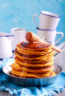 Stack of pancakes with honey in the pan