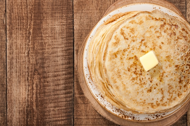 Stack of pancakes with oil, top view
