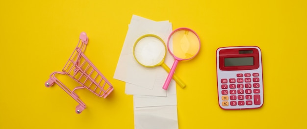Stack of paper checks, a pink plastic calculator and a magnifying glass on a yellow background. family budget audit concept, search for savings