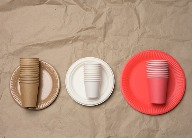 Stack of paper cups and round plates on a brown paper background. plastic rejection concept, zero waste