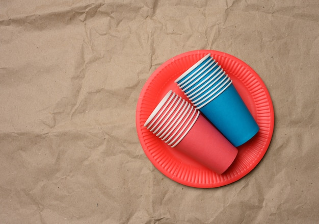 Stack of paper cups and round plates on a brown paper, top view