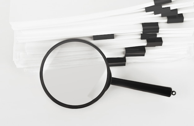Stack of paper documents with magnifying glass