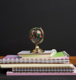 Stack of paper school notebooks and glass globe on black chalk board background, close up