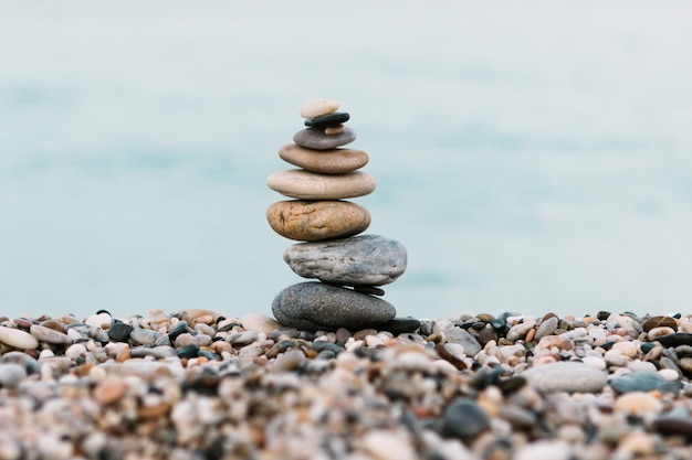 Stack of pebble stones on ocean background