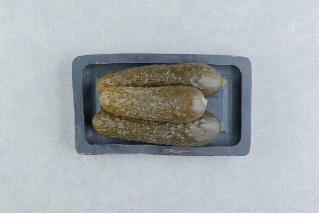 Una pila di cetrioli sottaceto su un tagliere