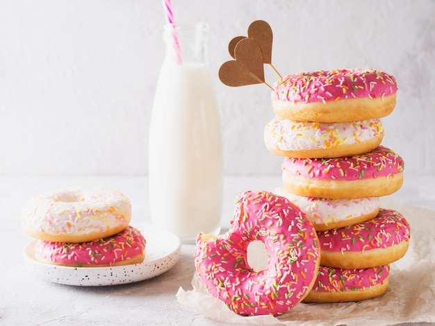 Stack of pink and white donats with bottle of milk over white