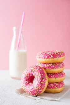Stack of pink and white donuts with bottle of milk over pink