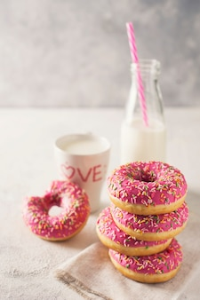 Stack of pink and white donuts with bottle of milk over white