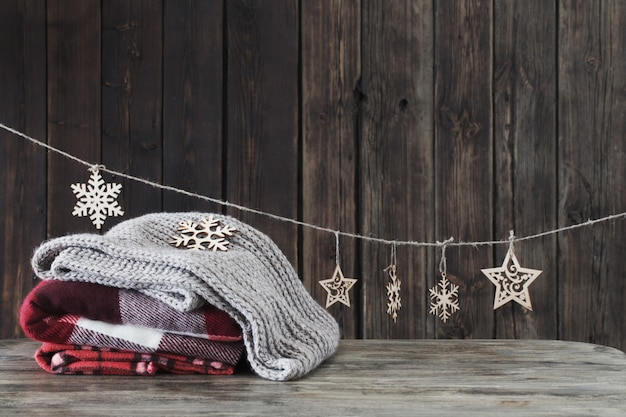Stack of plaids and christmas decorations on wooden background