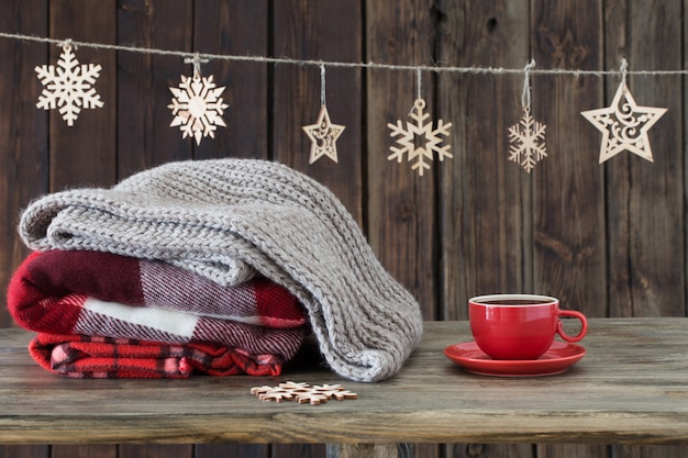 Stack of plaids, cup of tea  and christmas decorations on wooden background